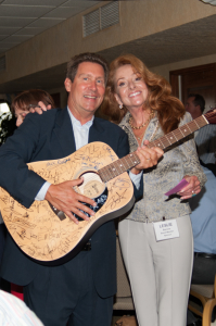 Don Diego Chair Paul Ecke III and Board member Leslie Barone display a Grandstand Stars autographed guitar up for bid.